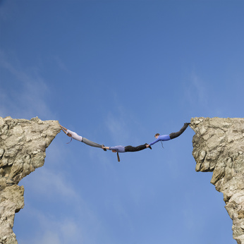 Businessmen holding hands and feet to bridge cliffs